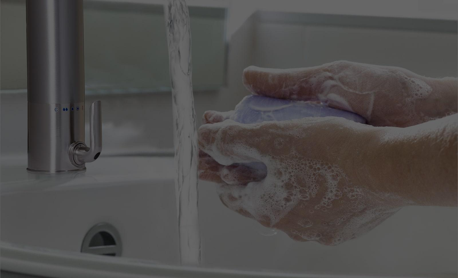 washing hands with warm water and soap in sink